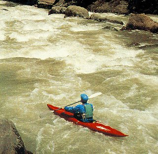Kayaker in churning waters of a Costa Rican river.