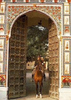 Rider pauses under a decorated arch.
