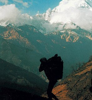 Porters carrying gear beneath snowcapped peaks.