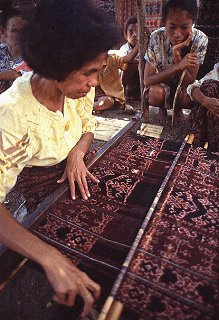 Woman displays Ikat weaving in Indonesia.