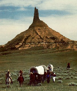 Wagon train beneath the spire of Chimney Rock.